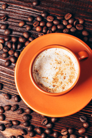 energizing: Ceramic orange cup of coffee with foam and coffee beans, lying on wooden table