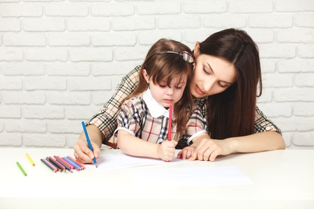 parental love: happy mother painting with her little daughter in the room with white table and bricked white wall, both girls are in checkered dresses
