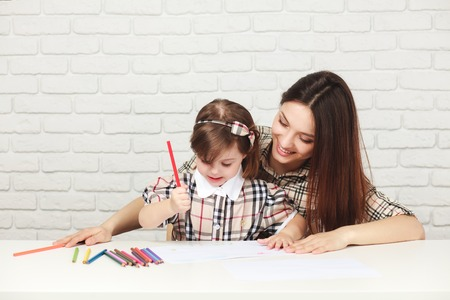 happy mother painting with her little daughter in the room with white table and bricked white wall, both girls are in checkered dresses Фото со стока - 46645712