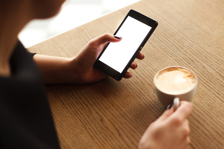 close in: Woman using a touch screen of smartphone on the wooden table, in cafe, near the window with cup of aromatic cappucino, close up Stock Photo