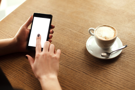 cappucino: Woman using a touch screen of smartphone on the wooden table, in cafe, near the window with cup of aromatic cappucino, close up Stock Photo
