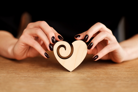 artistic design: Hands of beautiful woman holding wooden heart. Valentine concept Stock Photo
