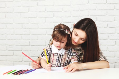 happy mother painting with her little daughter in the room with white table and bricked white wall, both girls are in checkered dresses
