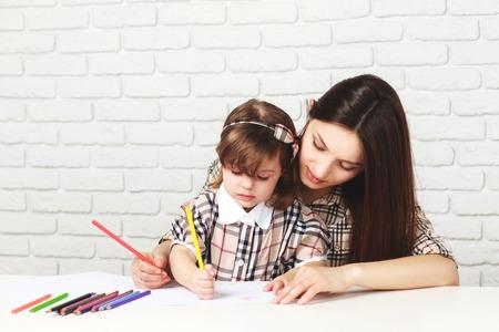 pintura madre feliz con su pequeña hija en la sala con una mesa blanca y pared blanca de ladrillo, ambas niñas están en vestidos a cuadros Foto de archivo