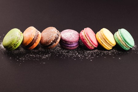 Row of french colorful macaroons with powdered sugar, lying on black background 免版税图像