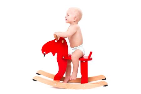juguetes: Divertido lindo beb� sentado en el caballo de juguete o alces y sonriente Foto de archivo