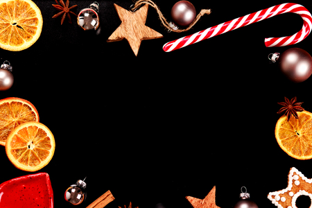 snaps: New year frame with black place for text or wishes. Sweets, cinnamon, dried oranges, toys, ginger snaps and spices.
