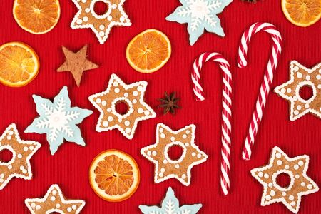 snaps: Christmas and new year holiday frame, made with sweets, stars, dried oranges, heart, cinnamon, beautiful ginger snaps - snowflakes and spices on red background.