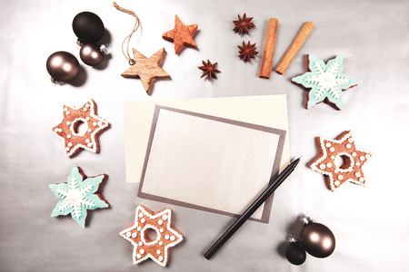 snaps: Christmas and new year holiday frame, made with sweets, stars, cup of coffee, heart, cinnamon, beautiful ginger snaps - snowflakes and spices on silver background. Sheet of paper and pen for writing goals or New Year wishes.