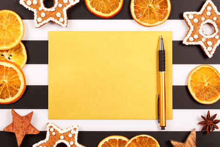 snaps: Christmas and new year holiday frame, made with stars, dried oranges, ginger snaps and spices on black and white background with lines. Sheet of paper and pen for writing goals or New Year wishes.