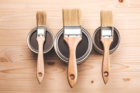 Copyspace with three paint brushes on three cans lying on wooden clean table. Top view Standard-Bild