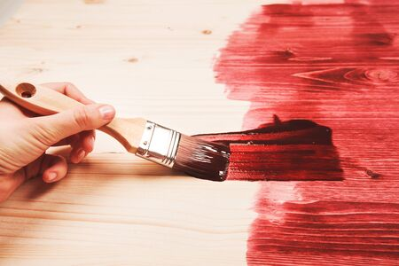 home decorated: Hand painting red color on wooden table use for home decorated. House renovation. Half - painted surface