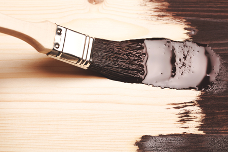 brush in: Varnishing natural wood with paint brush in brown color. Macro.