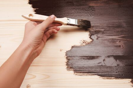 wooden surface: Half painted wooden surface. Hand varnishing or painting natural wood with paint brush and deep brown color. Stock Photo