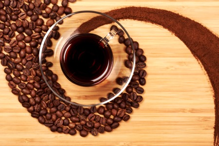 spiralling: Coffee beans and grains in the shape of a swirl and glass cup, lying on the wooden table. The way of coffee from beans to beverage. Three conditions or stages of coffee.