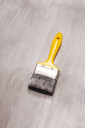 recently: Fresh painted wooden surface. White wooden table and yellow paint brush lying on it