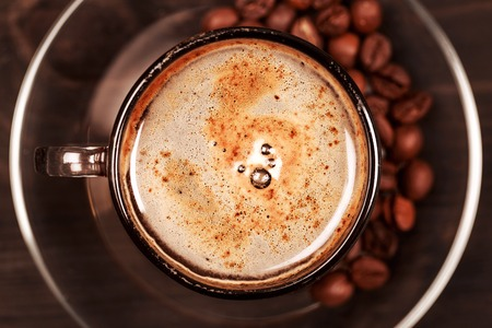 capuchino: Cup of cappucino with nice appetizing foam, standing on the saucer, on the dark wooden table. Top view, macro, closeup.