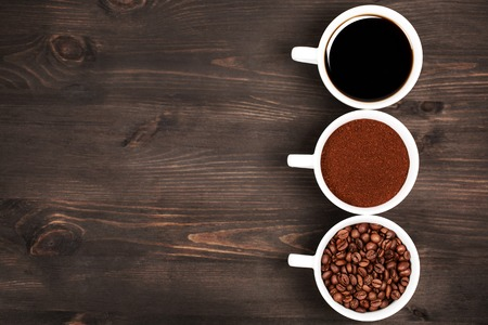 beverage in bean: Three cups with different states or stages, or conditions, or black coffee. Dark wooden background.
