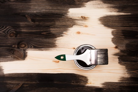 Paint brush on the can lying on wooden background. The surface is half - toned with red color. Stock Photo