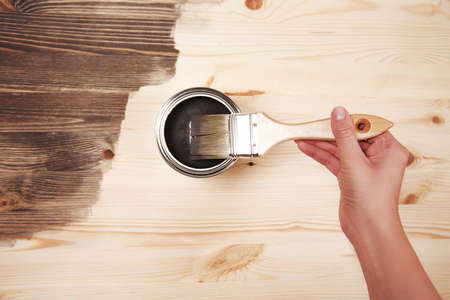 home decorated: Hand painting grey color on wooden table use for home decorated. House renovation. Half - painted surface. Smear of paint brush
