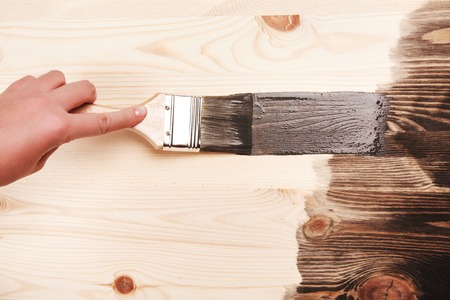 Hand painting grey color on wooden table use for home decorated. House renovation. Half - painted surface. Smear of paint brush