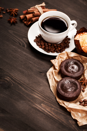 White cup of black coffee for breakfast with coffee beans and spices are standing on dark wooden table with pastry: cookies, brownie and muffin. Place for text