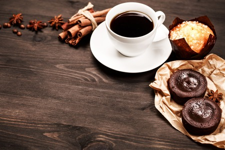 table grain: White cup of black coffee for breakfast with coffee beans and spices are standing on dark wooden table with pastry: cookies, brownie and muffin. Place for text