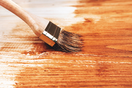 brocha de pintura: Varnishing a wooden shelf in brown using paintbrush