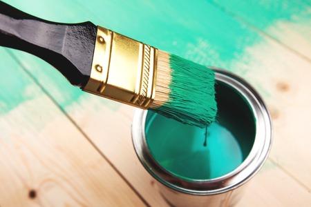 Varnishing a wooden shelf using paintbrush, turquoise color