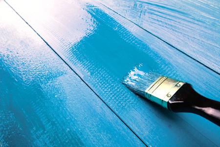 brocha de pintura: Pintura de un estante de madera usando la brocha, de color azul