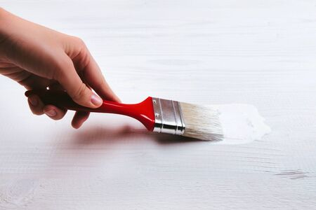 brush painting: Hand holding a brush applying varnish paint on a wooden surface