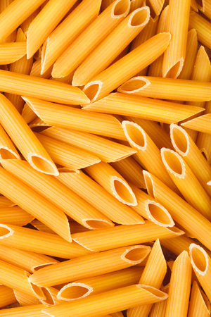 unboiled: Penne italian pasta as textured background, closeup. Stock Photo