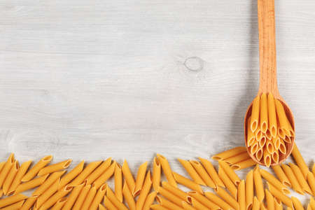 unboiled: Penne italian pasta lying in wooden spoon and on wooden table, forming textured frame background, closeup.