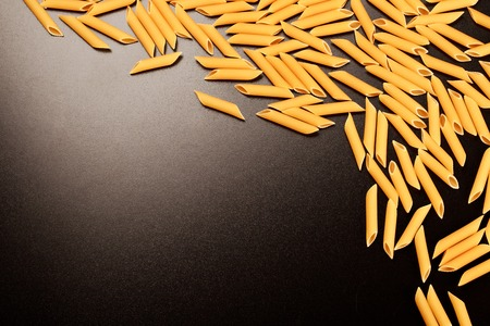 unboiled: Penne italian pasta forming textured frame on black background. Stock Photo