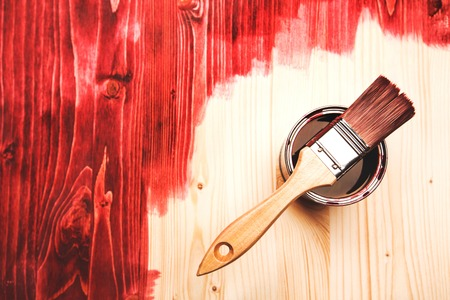 modernise: Paint brush on the can lying on wooden background. The surface is half - toned with red color. Stock Photo