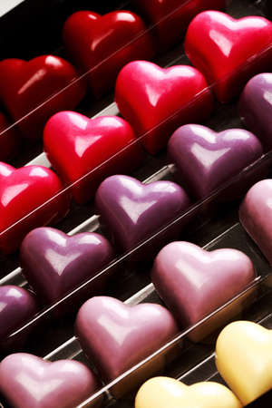 st  valentine's day: Black opened box with chocolate multicolored hearts, close up. St. Valentines Day Concept.