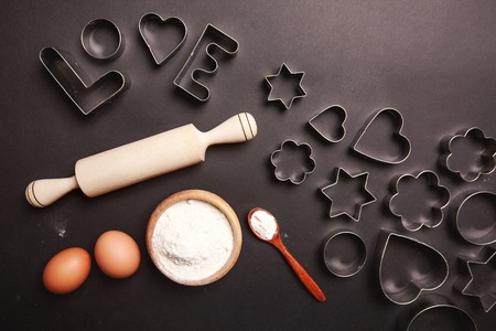 heart shaped stuff: Heart - shaped cookie cutters, flour and word Love, made with it, and other stuff for baking cookies, lying on black table.
