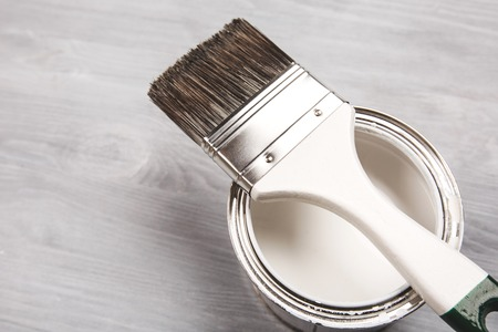 Copyspace with paintbrush and can with white paint lying on white wooden clean table. Stock Photo