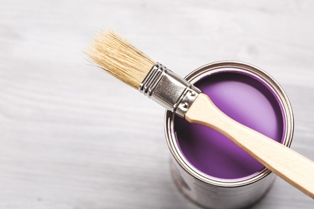 modernise: Copyspace with paint brush and can with violette or lavender paint lying on white wooden clean table. Stock Photo