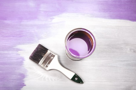 Paintbrush and can with lavender color lying on white wooden background.