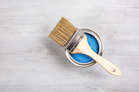modernise: Copyspace with paintbrush and can with blue paint lying on white wooden clean table.