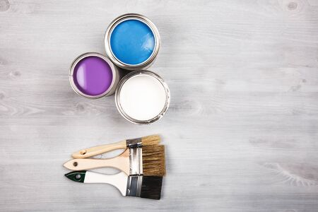 redecorating: House renovation, paint cans and colored brushes on white wooden background