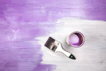 modernise: Paintbrush and can with lavender color lying on white wooden background. The surface is half - toned with violette color.