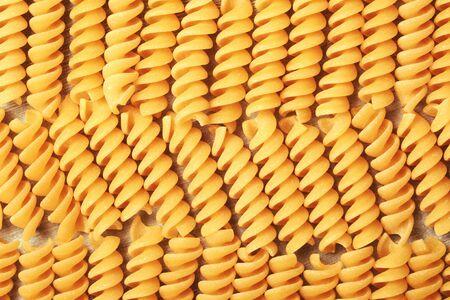 fusilli: Fusilli pasta forming textured background. Close up. Stock Photo