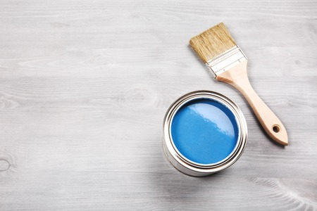 modernise: Copyspace with paintbrush and a can with blue paint lying on white wooden clean table. Stock Photo