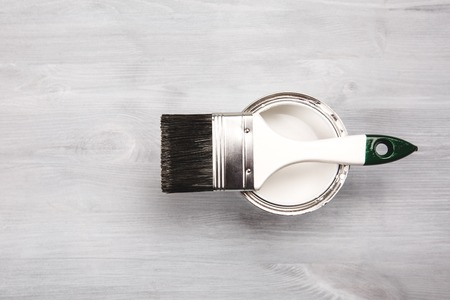 modernise: Copyspace with paintbrush and a can with white paint lying on white wooden clean table.