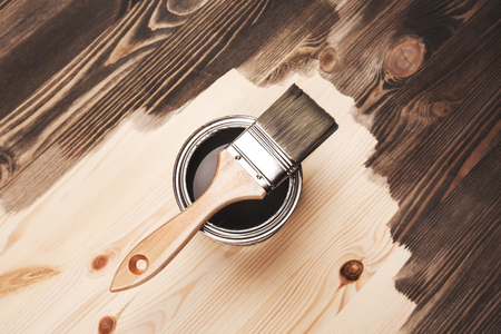 Paint brush on the can lying on wooden background. The surface is half - toned with grey color. Stock Photo