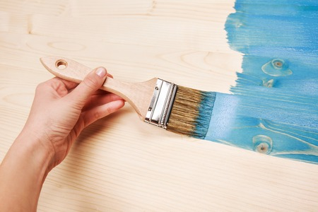 home decorated: Hand painting blue color on wooden table use for home decorated. House renovation. Half - painted surface. Smear of paint brush