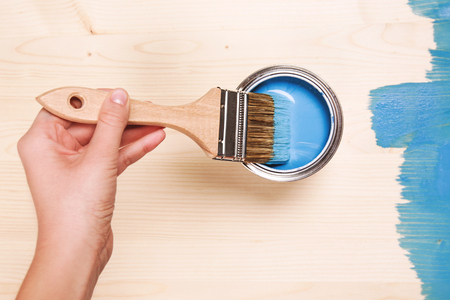 table surface: Hand painting blue color on wooden table use for home decorated. House renovation. Half - painted surface. Smear of paint brush