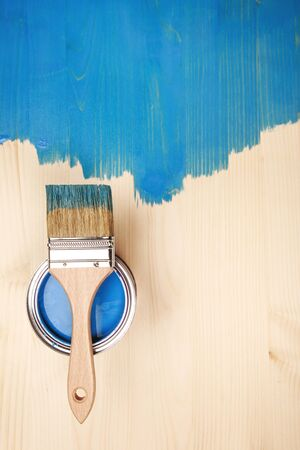 Paint brush on the can lying on wooden background. The surface is half - toned with blue color.